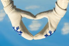 Female hands in the winter mittens in the shape of a heart on the cloudy blue sky. Concept. Female hands in the winter mittens in the shape of a heart on the sky stock image