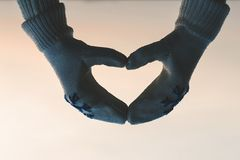 Female hands in the winter mittens in the shape of a heart on the cloudy blue sky. Concept. Female hands in the winter mittens in the shape of a heart on the sky stock images
