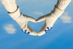 Female hands in the winter mittens in the shape of a heart on the cloudy blue sky. Concept. Female hands in the winter mittens in the shape of a heart on the sky royalty free stock images