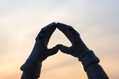 Female hands in the winter mittens in the shape of a heart on the cloudy blue sky. Concept. Female hands in the winter mittens in the shape of a heart on the sky stock photos