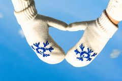 Female hands in the winter mittens in the shape of a heart on the cloudy blue sky. Concept. Female hands in the winter mittens in the shape of a heart on the sky royalty free stock photo