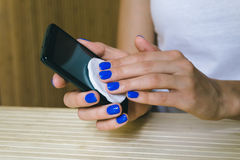 Female hands wipe dust touch screen mobile phone Stock Photos