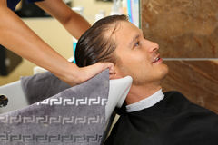 Female hands wiping hair of handsome smiling man with towel. After washing at hairdresser. Keratin restoration, latest trend, fresh idea, haircut picking Stock Images