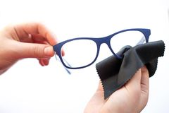 Female hands wiping spectacles with a microfiber fabric stock photos