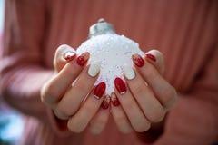 Free Female Hands With Stylish Holiday Manicure Holding Shiny White Christmas Bauble Stock Photos - 194506593