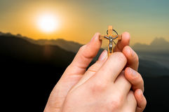 Female hands with wooden cross and sunset in the mountains. Religion concept Royalty Free Stock Photos