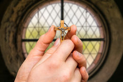 Female hands with wooden cross and window inside the church. Religion concept Royalty Free Stock Photos