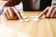 Female hands on a wooden office desk pick puzzle Stock Photo