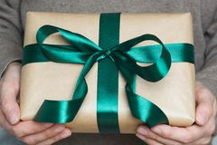 Female hands in woolen beige sweater holding beige box wrapped in craft paper with green ribbon. Close up Stock Image