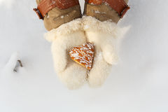 Female hands in woollen white mittens hold beautiful heart shape Stock Photography