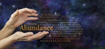 Cosmic Create Abundance Word Tag Cloud. Female hands with the word ABUNDANCE floating between surrounded by a relevant word cloud against a deep space blue stock photography