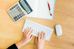 Female hands working at a keyboard,computer and stationery Royalty Free Stock Image