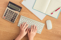 Female hands working at a keyboard,computer and stationery Stock Images