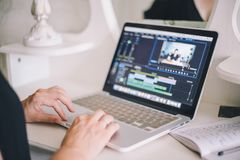 Female hands working on a laptop in a video editing program royalty free stock images