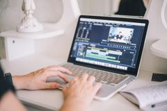 Female hands working on a laptop in a video editing program royalty free stock photography