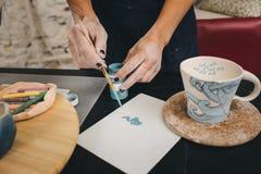 Female hands working on mug Stock Photos