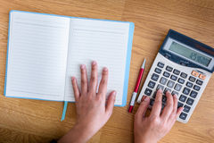 Female hands working notebook and calculator Royalty Free Stock Images