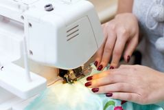 Female hands working on a sewing machine Royalty Free Stock Photos