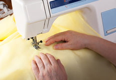 Female hands working on a sewing machine. Selective focus Stock Images