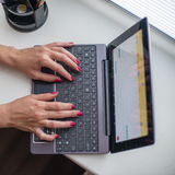Female hands working on ultrabook. On the windowsill Stock Images