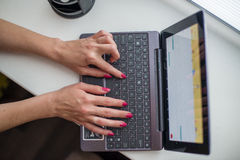 Female hands working on ultrabook. On the windowsill Stock Photos
