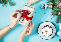 Female hands wrapping christmas gift box above blue table. Top view.  royalty free stock image