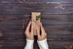 Female hands wrapping christmas gift box above wooden table. Top view.  royalty free stock images