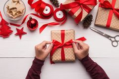 Female hands wrapping christmas gift box top view stock photography