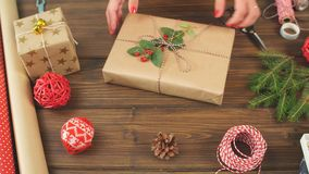 Female hands wrapping Christmas gift in craft ecological paper on dark wooden backround stock video footage