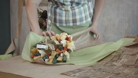 Female hands wrapping edible bouquet in kraft paper. Closeup of female hands packing delicious edible bouquet arrangement with assorted types of cheese, cherry stock video footage