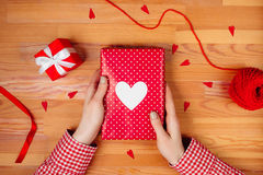 Female hands wrapping gift on wooden table. Female hands are wrapping a christmas gift on wooden background Royalty Free Stock Images