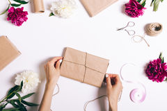 Female hands wrapping presents on a white table. Top view Stock Images