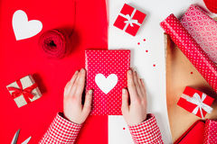 Female hands are wrapping a valentines gift on red. Female hands are wrapping a christmas gift on red  white table Royalty Free Stock Photos