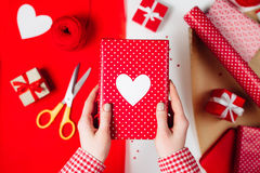 Female hands are wrapping a valentines gift on red. White table Stock Photography