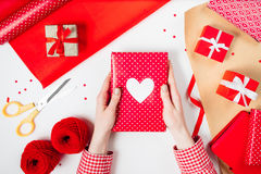 Female hands are wrapping a valentines gift on red. White table Stock Photo