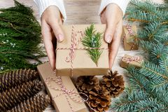 female hands wrapping xmas gifts into paper and tying them up with red threads royalty free stock images