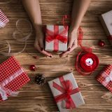 Female hands wrapping xmas gifts into paper and tying them up with red and white threads Royalty Free Stock Image