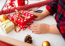 Female hands wrapping xmas gifts into paper and tying them up wi Royalty Free Stock Photography