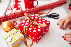 Female hands wrapping xmas gifts into paper and tying them up wi Stock Photo