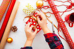 Female hands wrapping xmas gifts into paper and tying them up wi. Th gold threads Royalty Free Stock Photos