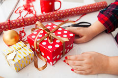 Female hands wrapping xmas gifts into paper and tying them up wi Royalty Free Stock Photo