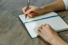 Female hands are writing in a notebook. Female hands writing information in a notebook on the table in the office royalty free stock image