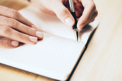 Female hands writing in notebook with pen on wooden table Stock Photo