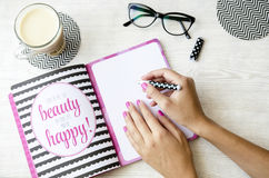 Female hands writing in notebook with quotes on wooden table with ice coffee and glasses. Top view vintage style Royalty Free Stock Image