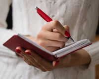Female hands writing in a notebook. Female hands with red nails write in a notebook Stock Image