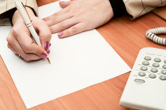 Female hands writing on white paper. Stock Images