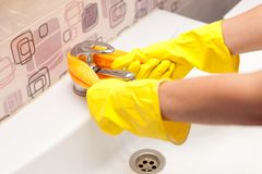 Female hands with yellow rubber protective gloves cleaning tap with orange cloth Royalty Free Stock Images
