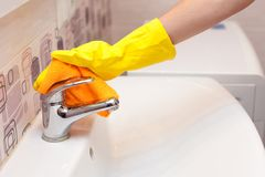 Female hands with yellow rubber protective gloves cleaning water tap with orange cloth Royalty Free Stock Image