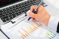 Female handwriting. Close up of businessperson analyzing statistical data Royalty Free Stock Photography