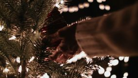 Female hanging Christmas ball on tree and glow bokeh lights.  stock video footage